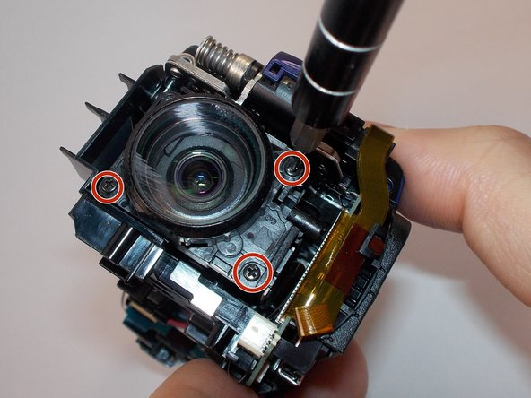 Remove the 3 (4mm) screws on the front of the lens using the Philips #0 Screwdriver.
