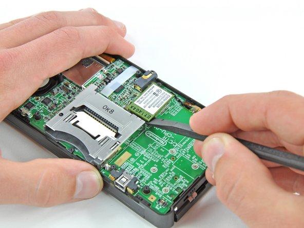 Schiebe das flache Ende des Spudgers unter die Ecke der Wi-Fi Karte und hebe sie von der Hauptplatine weg.