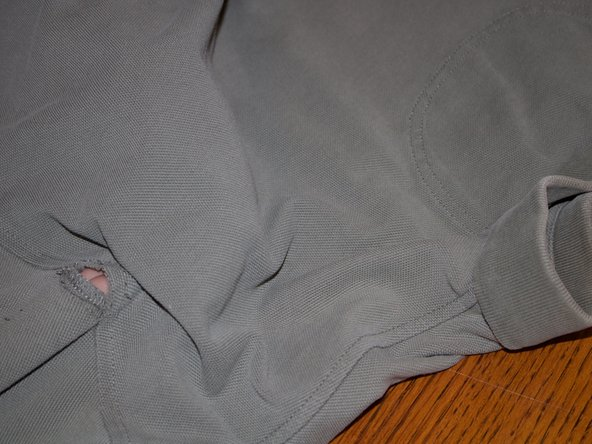 After you have found the hole put your hand underneath. Get the needle and thread and from underneath the shirt, start putting the needle through the shirt.