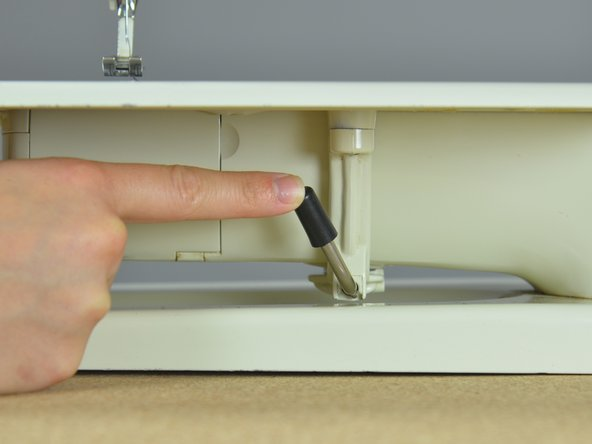 Lock the sewing machine table into place by pushing the clamp lever to the right until it engages.