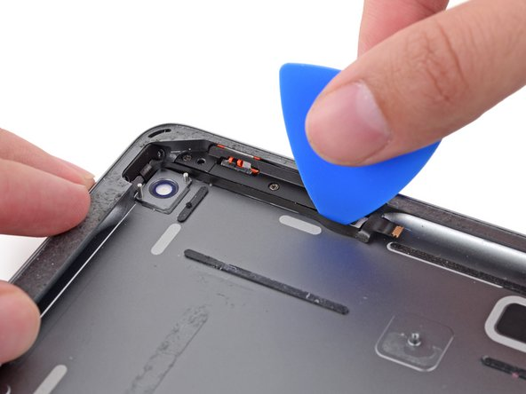 Carefully insert an opening pick between the power button ribbon cable and the edge of the case.