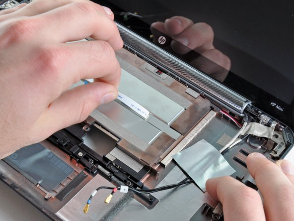 Peel and de-route the SIM card ribbon cable from its channel on top of the underside of the battery compartment.