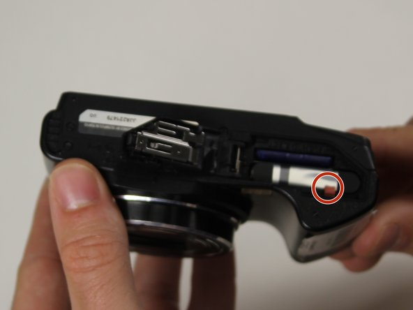 Push down on the red retaining button to release the battery.