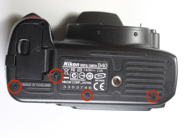 Remove the four highlighted 3.0 mm Philips #0 screws on the bottom of the camera.