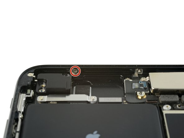 Remove the 1.3 mm Phillips screw securing the antenna component to the top edge of the rear case.