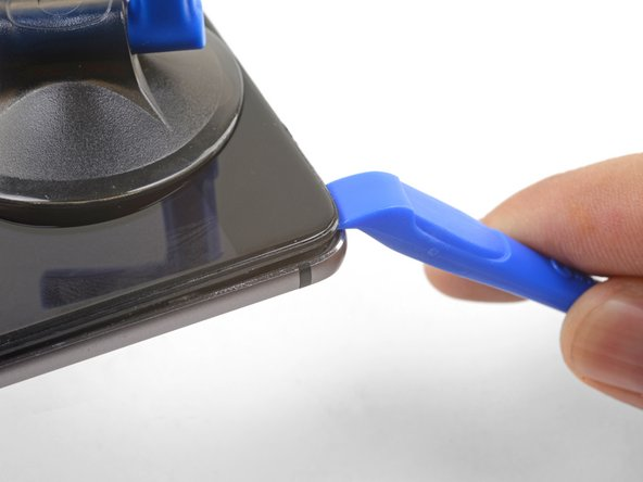 Once the opening tool's edge is wedged in position, carefully slide the tool along the bottom edge of the phone.