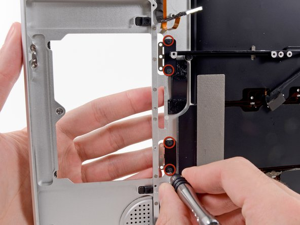 To replace the trackpad brackets, you must first remove the black covers that hold them to the upper case.