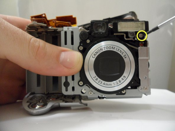 Unscrew the 3.8 mm screw under the flash housing.