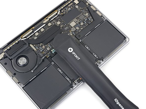 Prepare an iOpener and lay it on top of the trackpad ribbon cable for about a minute, in order to soften the adhesive securing the trackpad ribbon cable to the top of the battery.