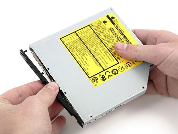 Carefully remove the bezel from the optical drive, minding the two plastic tabs on the bottom, which may catch.