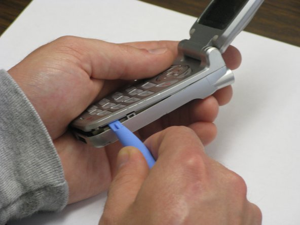 With the phone flipped open, wedge the back cover from the faceplate by running the tip of the plastic opening tool around the seam on the back of the phone.