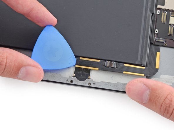 Finally, slide the opening pick between the battery and the Lightning connector itself to separate the last of the adhesive underneath the cable.