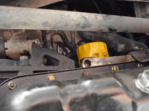 Locate the oil filter. It is on the driver's side of the car, on the back side of the engine and above the oil drain plug.