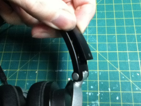 After removing the two small screws, try closing the headband to it's shortest position. The outer panel will pop out toward the bottom edge.