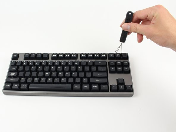 Insert the keycap puller around the key you'd like to install an O-ring under.