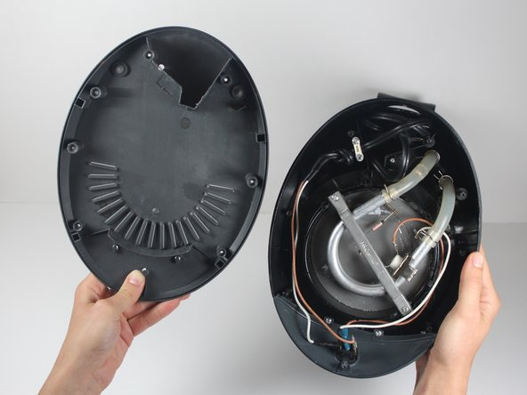 Gently lift the base cover to expose the inside of the coffee machine.