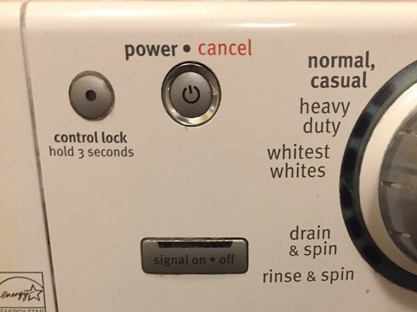 "The power button contains  a gray colored round button actuator in a chrome housing.  The words ""Power -  Cancel"" (solid dot between words) are printed above the button"
