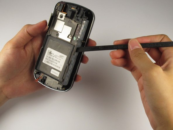 Lift up and loosen the metallic silver trim on the perimeter of the phone using a nylon spudger.