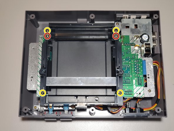 Remove four 13.25mm Phillips screws from the four corners of the cartridge tray.