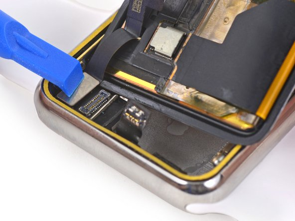 Use a plastic opening tool to reconnect the display data and digitizer cable connectors.