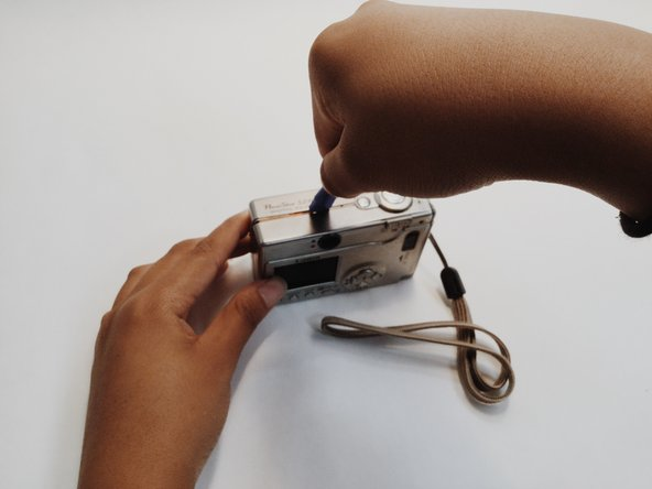 Use a pry tool to open the outer casing of the camera and access the internal components.