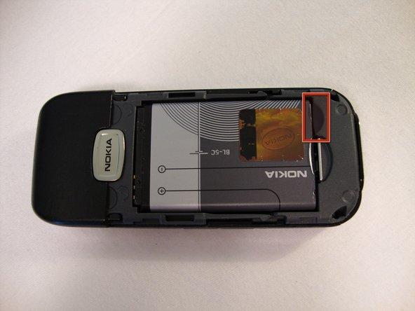 Utilisez un ongle et tirez délicatement le bas de la batterie vers le haut.