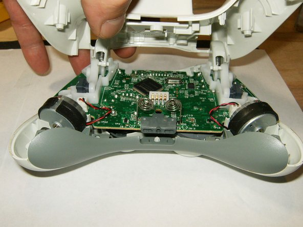 Tilt the bottom case slightly toward the trigger buttons to slide it off the top case