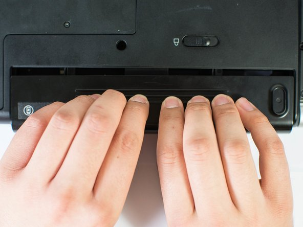 Remove the battery using two hands and pull it away from the computer.