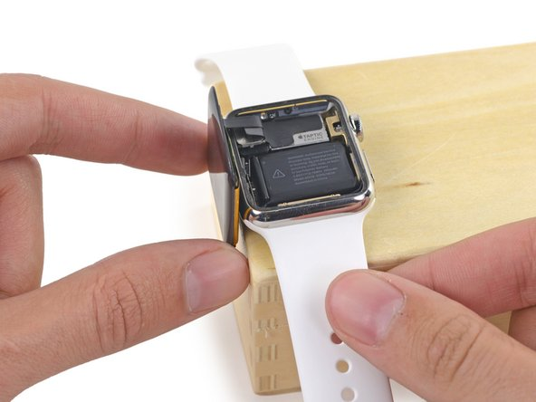 "Place the watch on an elevated surface, at least 1/2"" or 1 cm tall—a small box or the edge of a book will work great. This will allow the screen to hang down vertically and give better access to the battery."