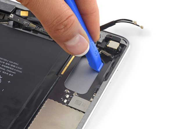 Insert an opening tool underneath the logic board on the other side of the rectangular cut out and pry it up.