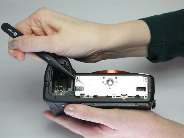 Remove metal plate. Sometimes this plate can become stuck and hard to remove. Use tweezers to separate the plate from the bottom of the camera.