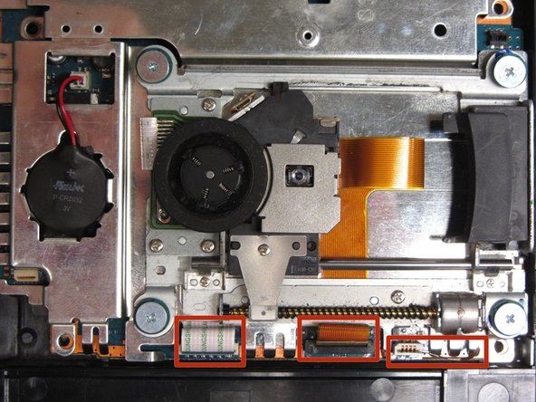 Locate the three ribbon cables connecting the optical drive to the motherboard.