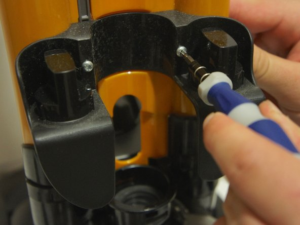 Using a T15 Torx Security Screwdriver, remove the screw on each side of the indention in which the hose normally rests.