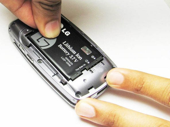 Slide a tool or finger into the notch at the top of the battery  to carefully remove it.