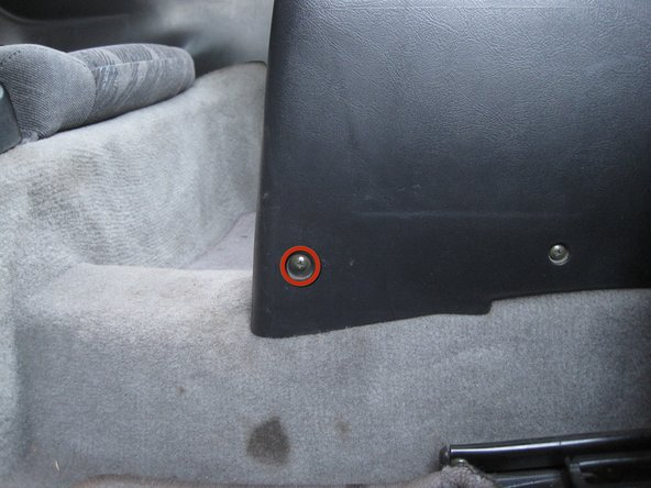 Remove the two Phillips screws at the very rear of the center console near the floor.