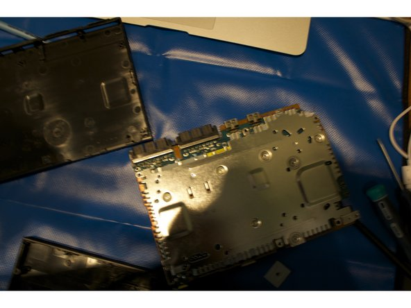 Gently lift the metal casing from the motherboard. Place it to the side.