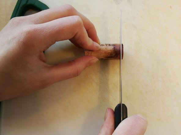 Using a serrated knife (such as a steak knife), cut the cork horizontally along your mark.
