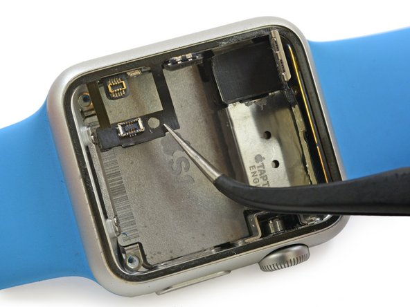 Given the limited amount of space inside the Apple Watch, we find the microphone ribbon cable creatively ensnared between the inner and outer layers of the case.