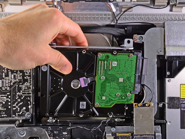 Slightly rotate the hard drive out of the outer case and lift it up off its mounting pins toward the top edge of the iMac.