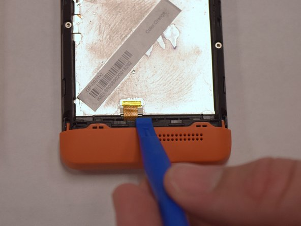 Insert the plastic opening tool into the groove between the bottom of the phone and the battery.