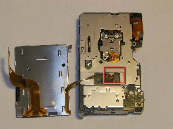 The screen is now connected only by a small cable that runs to the rear board of the camera. Using tweezers, slowly pull the cable out of the connector.