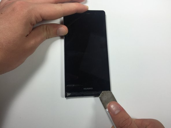 Use the iSeasmo tool to wedge between the screen and the plastic near the bottom right corner of the phone. You must wedge the iSeasmo underneath the white plastic part of the screen, and not just the glass.