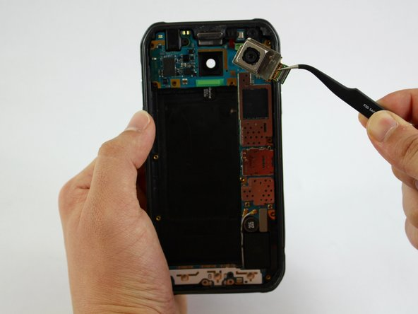 Use the tweezers to remove rear camera from motherboard.