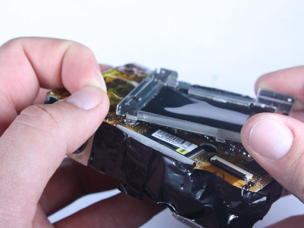 Remove the medal housing from the logic board by carefully peeling the yellow tape off of the metal housing.