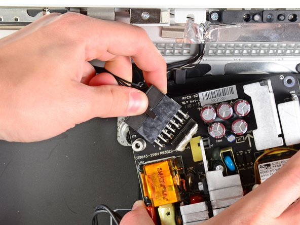 Carefully lift the power supply out of the outer case and rotate it to expose the cable lock as shown, minding the DC-out and AC-in cables still attaching it to the iMac.