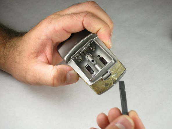 With the pick side of a spudger (or tweezers), peel the sticky tape from the device.