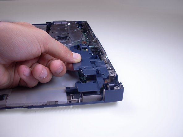 Remove blue plastic piece by gently pulling away from adaptors on the back of the laptop.