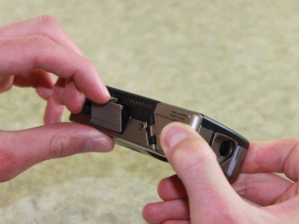 Tirez la languette du couvercle de la batterie vers le haut et appuyez dans le sens indiqué par la flèche sur la languette.