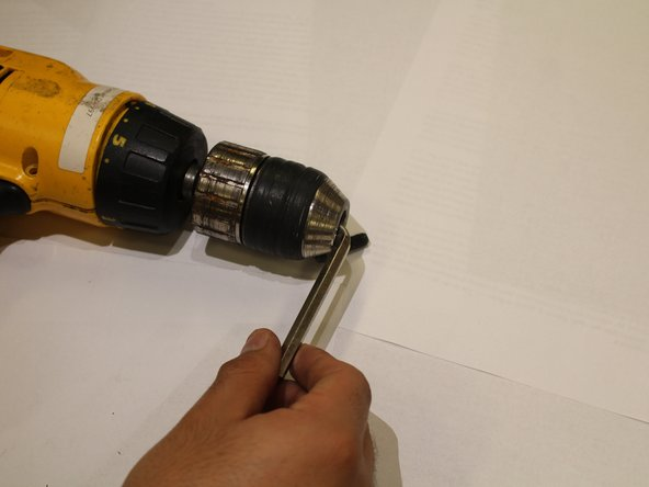 Infila una chiave a brugola nel mandrino e girala in senso orario per stringere la chiave.