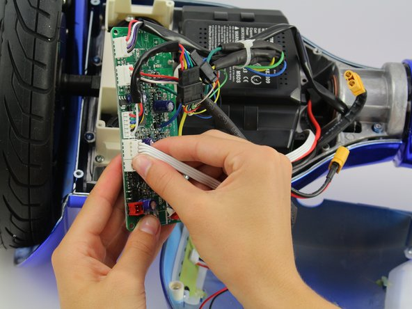 Unplug the white wires by squeezing the connector and pulling away from the board.